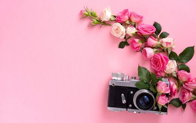 Composición floral con una corona de rosas rosadas y cámara retro sobre fondo rosa. fondo de san valentín. vista plana, vista superior.