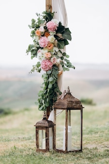 Composición floral hecha de eucalipto y tiernas flores rosadas con velas al aire libre