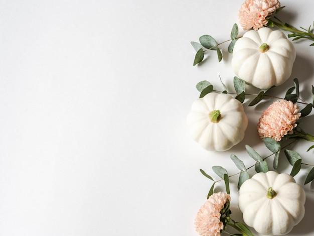 Composición floral de otoño de calabazas blancas, asters de durazno y eucalipto sobre un fondo blanco.