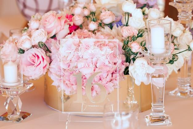 Composición floral y placa de vidrio transparente grabado entre velas.