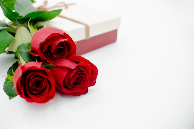 Composición de flores con caja de regalo hecha de flores color de rosa sobre fondo blanco