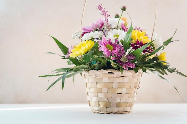 Composición de flores en canasta de mimbre en mesa