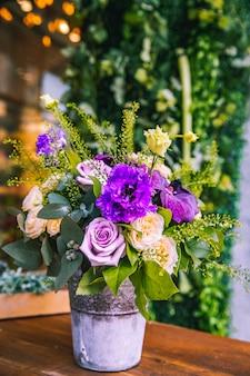 Composición de flores en el cubo de crema y rosas moradas vista lateral lithianthus