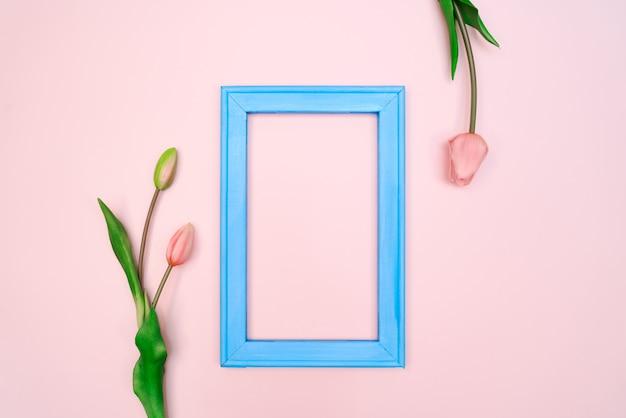 Composición de flores flores de tulipán con marco de fotos azul en rosa