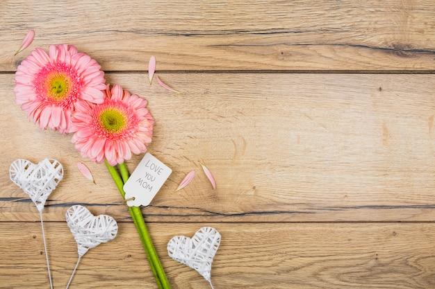 Composición de flores frescas con etiqueta cerca de corazones ornamentales en varitas