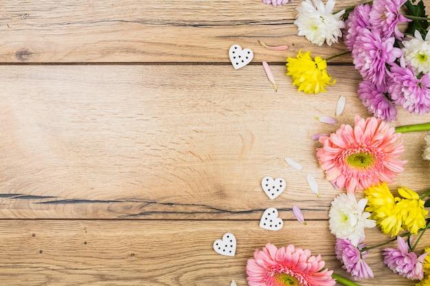 Composición de flores frescas junto a corazones ornamentales.