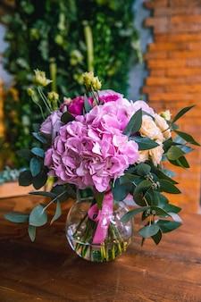 Composición de flores en jarrón de cristal hortensias rosas naranjas brillantes vista lateral