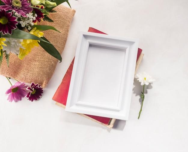 Composición de flores y marco de fotos en escritorio gris.