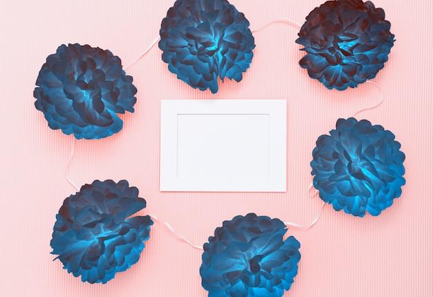Composición con flores de papel y marco blanco con espacio en blanco para texto