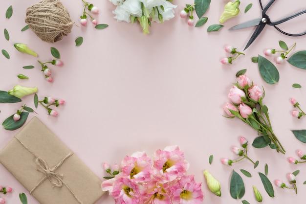 Composición de flores con regalo sobre fondo rosa blanco. vista plana, vista superior.
