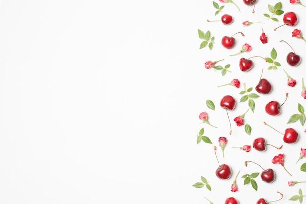 Composición de flores rojas, cerezas y hojas verdes.