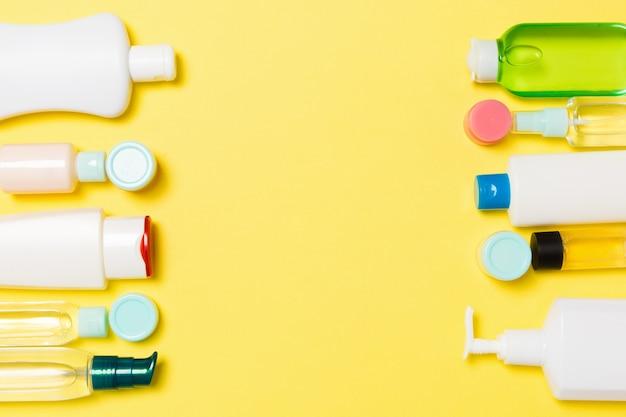 Composición de frascos y botellas de cosméticos de diferentes tamaños sobre fondo amarillo