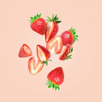 La composición de las fresas. cortar fresas en trozos volando en el aire