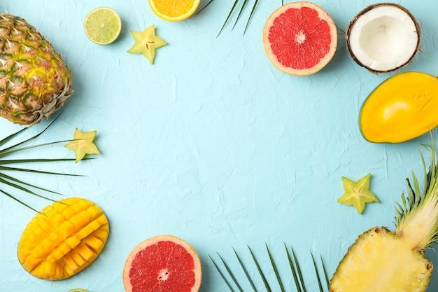 Composición con frutas exóticas sobre fondo azul, espacio para texto