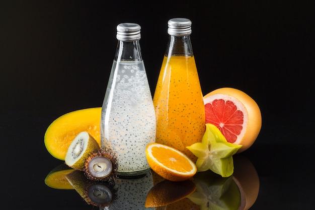 Composición de frutas y jugos sobre fondo negro
