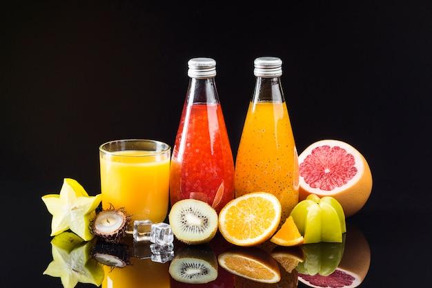 Composición de frutas y jugos sobre fondo negro.