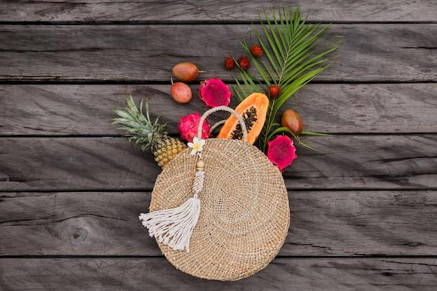 Composición con frutas tropicales en bolsa de paja
