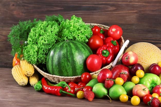 Composición con frutas y verduras frescas en mesa de madera
