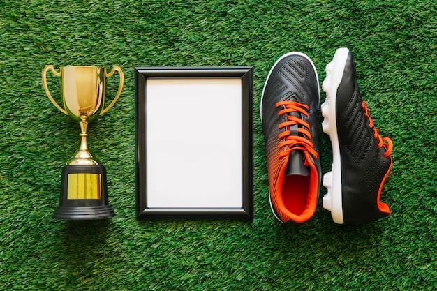 Composición de fútbol con marco al lado de trofeo y zapatos