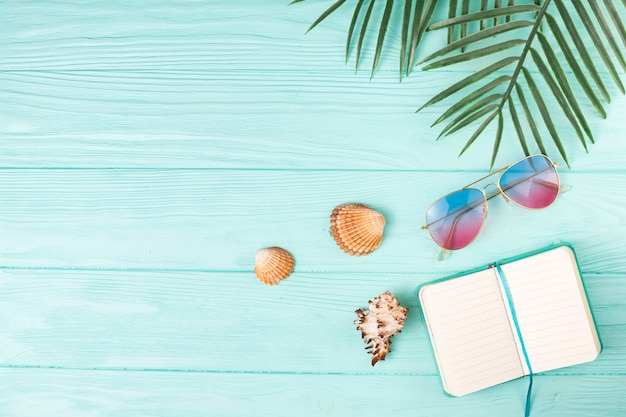 Composición de gafas de sol con cuaderno y hojas de palma.