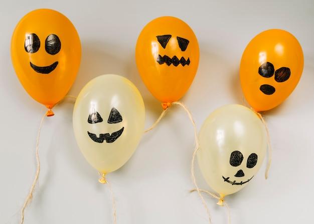 Composición con globos naranjas y blancos con caras espeluznantes