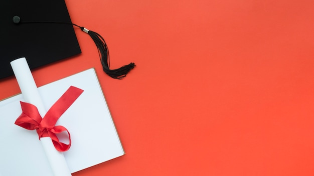 Composición de graduación festiva sobre fondo rojo con espacio de copia
