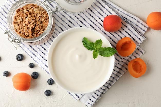Composición con granola, yogurt y frutas frescas sobre fondo de cemento blanco