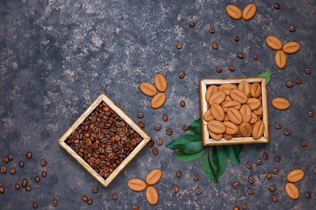 Composición con granos de café tostados y galletas con forma de grano de café sobre una superficie de color marrón oscuro