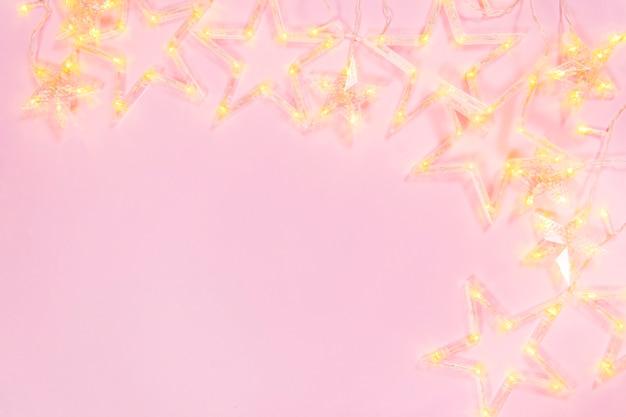 Composición guirnalda ligera a sobre fondo rosa. marco de guirnalda estrella sobre fondo rosa