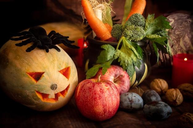 Composición de halloween con arañas de calabaza manzanas velas y verduras