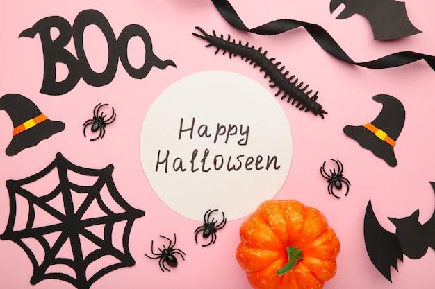 Composición de halloween con arañas y murciélagos sobre fondo rosa pastel.