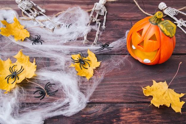 Composición de halloween. calabaza naranja, esqueletos, hojas secas amarillas, arañas negras en la web sobre fondo de madera oscura.