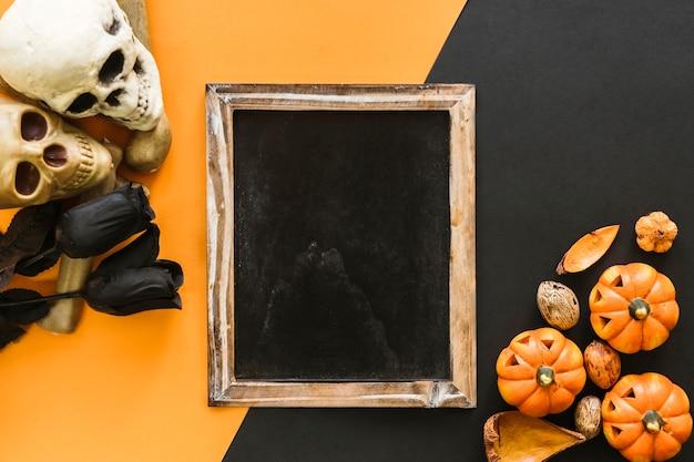Composición de halloween con pizarra, calabazas y rosas negras