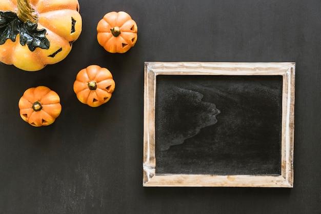 Composición de halloween con pizarra y calabazas