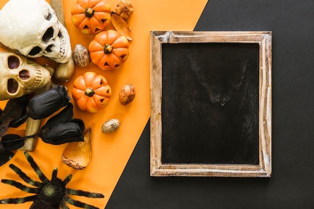 Composición de halloween con pizarra, cráneos y araña