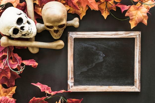 Composición de halloween con pizarra y cráneos y hojas de otoño