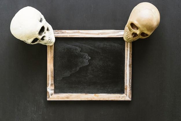 Composición de halloween con pizarra y dos cráneos