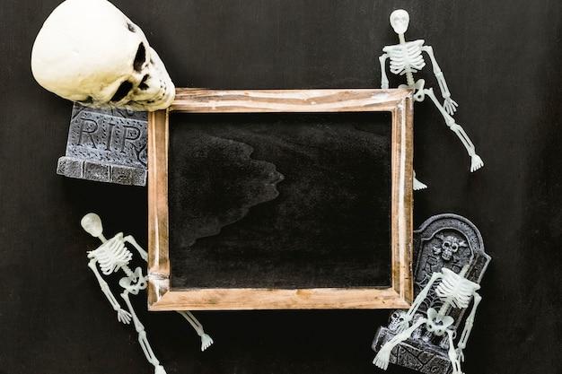 Composición de halloween con pizarra, esqueletos y cráneo