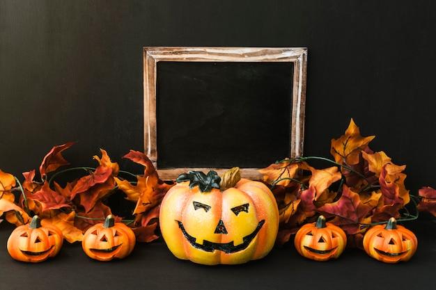 Composición de halloween con pizarra, hojas de otoño y calabaza