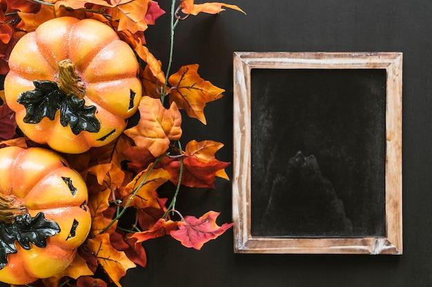 Composición de halloween con pizarra y hojas de otoño