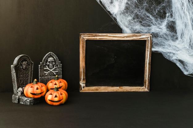 Composición de halloween con pizarra y telaraña