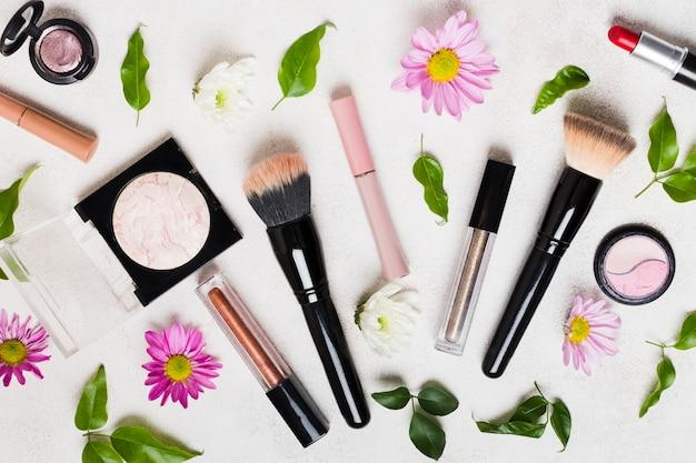 Composición de herramientas de maquillaje y flores.