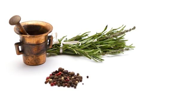 Composición de hierbas aromáticas: romero y tomillo, pimienta negra, rosa y blanca, mortero de cobre para condimentos, primer plano