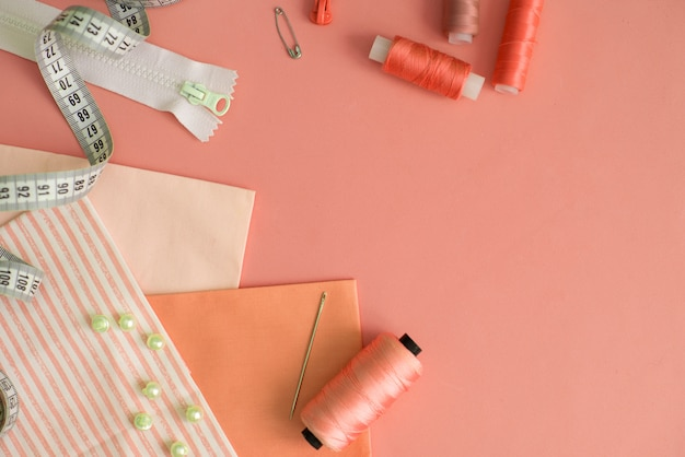 Composición con hilos y accesorios de costura sobre fondo de color, plano.