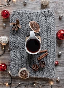 Composición hogareña acogedora con una taza de té en un elemento de punto, detalles de decoración navideña, endecha plana.
