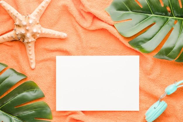 Composición de hoja de papel blanco auriculares y hojas de mar.
