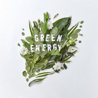 Composición de hojas verdes, flores blancas y un tulipán con la inscripción energía verde sobre un fondo gris con espacio de copia. el concepto de conservación del medio ambiente. endecha plana