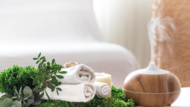 Composición con humidificador de aire y accesorios de baño sobre un fondo borroso.