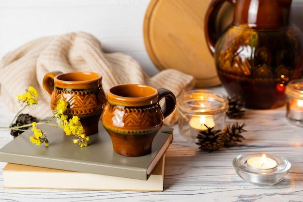 Composición de hygge con dos tazas rústicas, libros y velas en la mesa de cocina de madera con jarra.