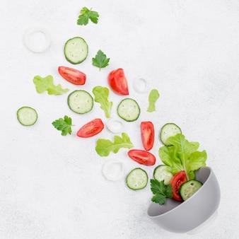 Composición de ingredientes de ensalada sobre fondo blanco.